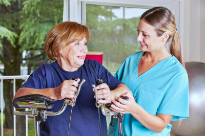 caregiver assisting senior woman in therapy