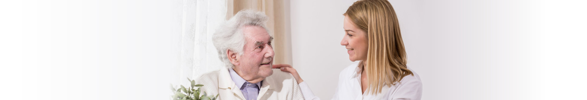 elderly man and caregiver smiling with each other